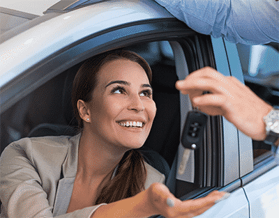 Image of locksmith handing a client her car keys after getting her back in her car.